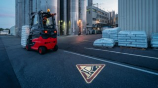 Zum umfassenden Angebot an Sicherheitsfeatures auf der Fachmesse A+A gehört der Linde TruckSpot. Per LED-Technik wird ein rotes Warndreieck auf den Boden projiziert und macht Fußgänger oder andere Staplerfahrer sehr deutlich aufeinander aufmerksam.